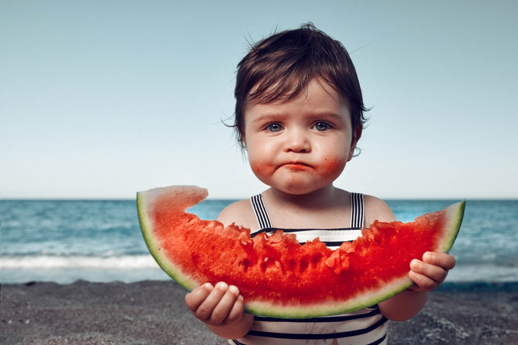 funny little girl on the beach eating watermelon
